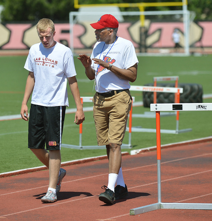 . Connor Speck, left, 17, of Walnut Creek, gets expert advice after running the hurdles from Tom Hill, right, a 1972 bronze medalist in the hurdles, during the Eddie Hart All-In-One Foundation track and field clinic at Pittsburg High School in Pittsburg, Calif., on Saturday, May 4, 2013. (Dan Rosenstrauch/Bay Area News Group)