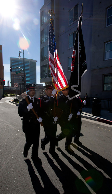 ". An Oakland Fire Department color guard preceeds a fire truck bearing a fragment of steel from the twin towers of the World Trade Center, at a ceremony to dedicate the final section of ""Remember Them,\"" artist Mario Chiodo\'s paean to heroes of civil rights and humanity, Thursday, Feb. 21, 2013 in Oakland Calif. (D. Ross Cameron/Staff)"
