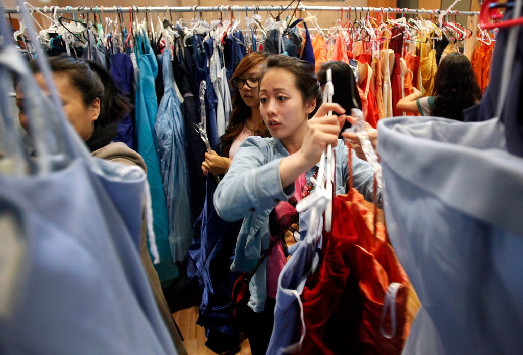 . Linda Tran searches through the racks at Operation Prom Dress, holding its fifth annual event Sunday, March 10, 2013 at Seven Trees Community Center in San Jose, Calif. 800 girls had a chance to pick a prom dress without any worry about the expense. Since 2009, the office of Vice Mayor Madison Nguyen has given out more than 3000 dresses. (Karl Mondon/Staff)