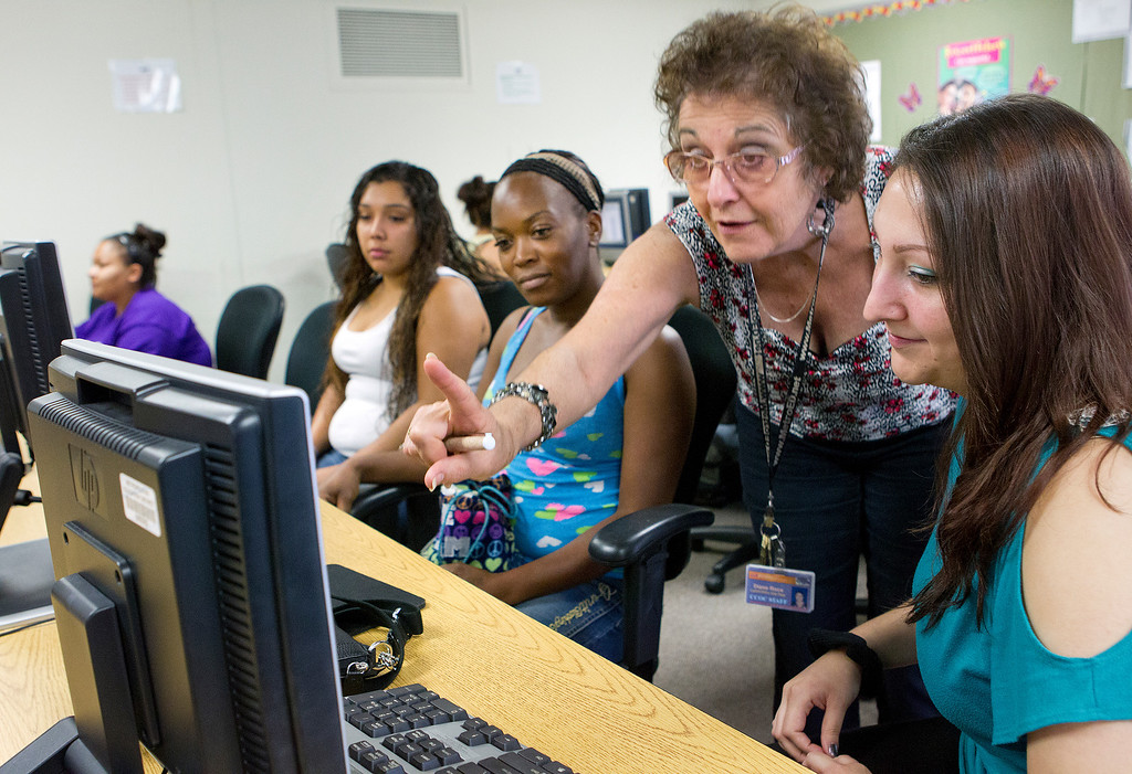 . CalWorks site representative Diana Roca, standing in center, helps Krystle Aguilar, 22, right, and Tomara Fingers, 36, center, troubleshoot a computer problem as they prepare to study for the GED at the computer lab of the Metropolitan Adult Education Program (MetroED) in San Jose, Calif. on Tuesday, July 2, 2013.  (LiPo Ching/Bay Area News Group)