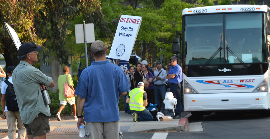 . Two BART strikers stand and look towards a long line of commuters working their way down California Boulevard  to a line of buses waiting to take them to San Francisco on the second day of the BART strike in Walnut Creek, Calif., on Tuesday, July 2, 2013.  (Dan Rosenstrauch/Bay Area News Group)