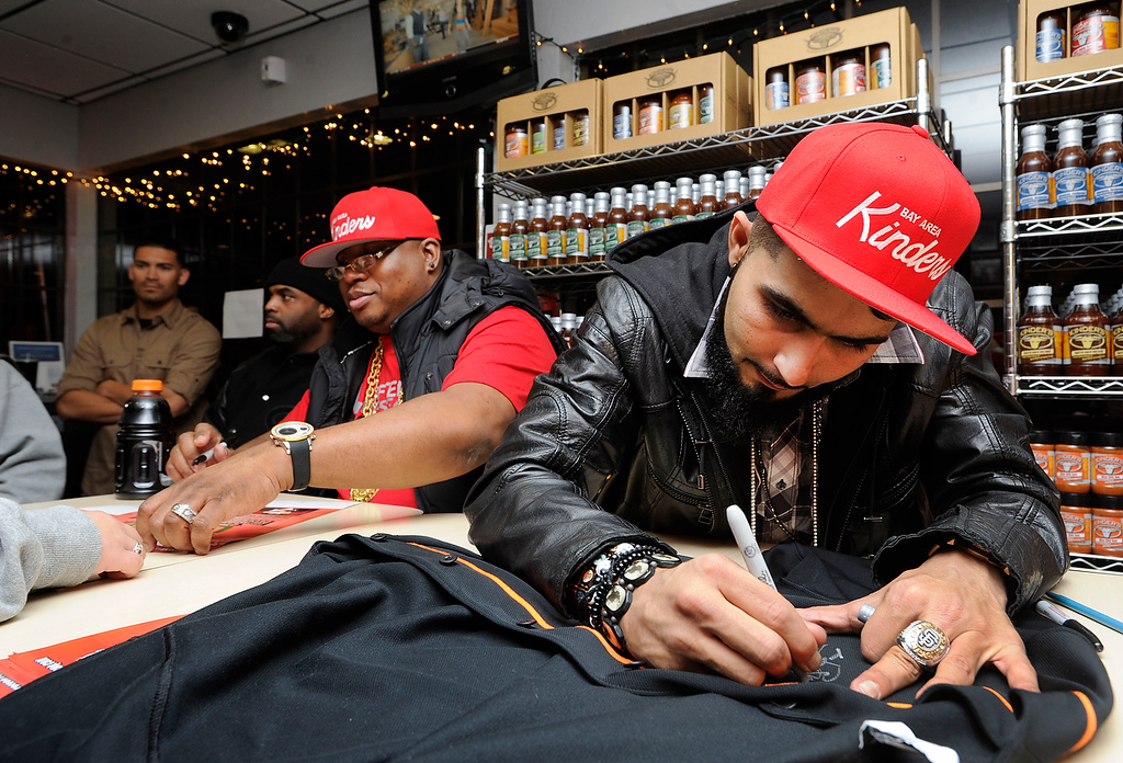 . Rapper E-40, left, and Giants Reliever Sergio Romo sign autographs at a Marines Corps Reserve Toys For Tots event held at Kinder\'s Meats and Deli on Wednesday, Dec. 12,  2012, in Pleasant Hill, Calif. (Susan Tripp Pollard/Staff)