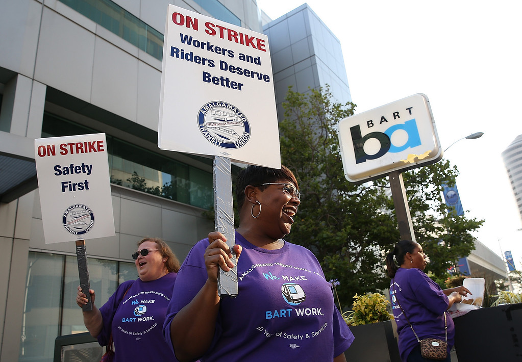 . Amalgamated Transit Union workers hold signs as they strike outside of a Bay Area Rapid Transit (BART) station on July 1, 2013 in Oakland, California.(Photo by Justin Sullivan/Getty Images)