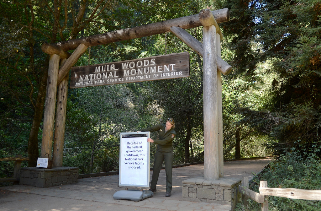 ". Park ranger Sam Bell places a closed sign at the entrance to Muir Woods National Monument in Mill Valley, Calif. on Tuesday, Oct. 1,  2013. The sign reads, ""Because of the federal government shutdown, this National Park Service facility is closed.\"" (Alan Dep/Marin Independent Journal)"