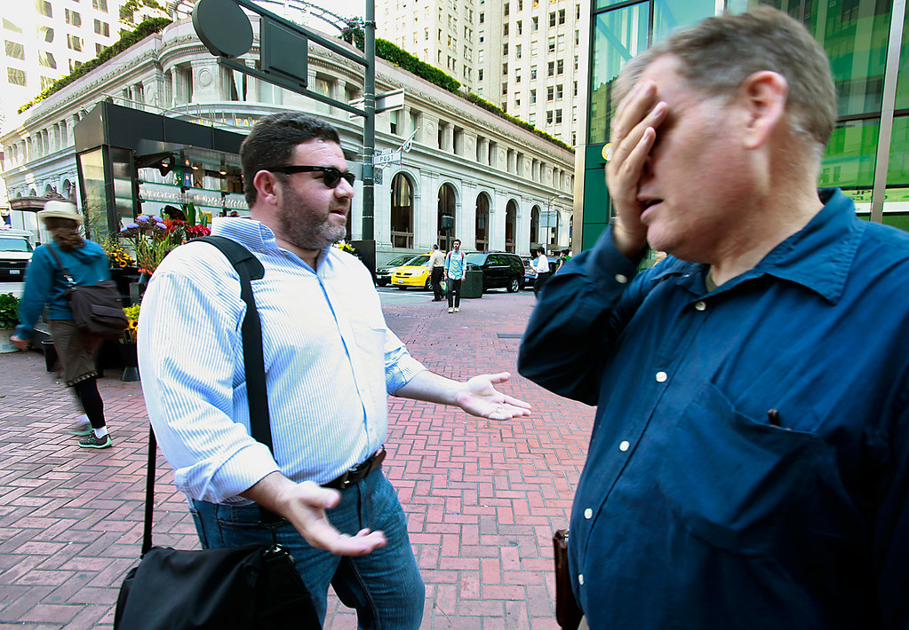 . Bay Area News Group reporter Thomas Peele (right) lost  his bet with colleague Josh Richman who beat him by driving his car from the Fremont BART station to downtown San Francisco Monday morning, July 1, 2013, the first day of the BART strike.  Peele took public transit which took longer than two and one-half hours. (Karl Mondon/Bay Area News Group)