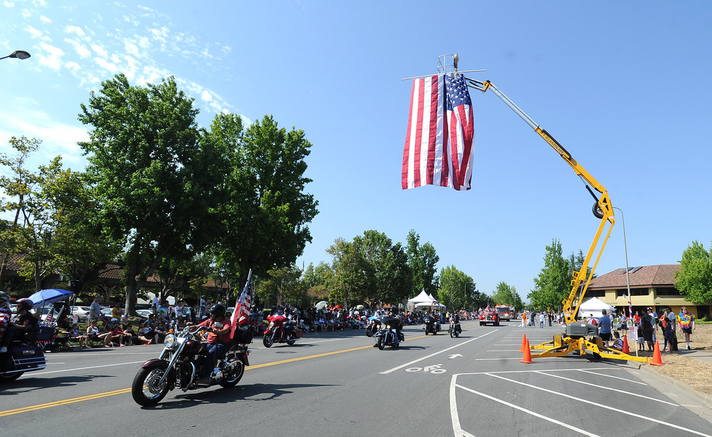. Participants go under a large American flag during the Fourth of July parade in Fremont, Calif., on Thursday, July 4, 2013. The parade featured more than 70 entries. (Dan Honda/Bay Area News Group)