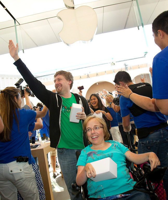 . Mario Panighetti and Jenny Mitchell, left to right, who were fourth and fifth in line, are greeted by Apple store staff as they enter the redesigned Apple Store at the Stanford Shopping Center in Palo Alto, Calif., on Saturday, Sept. 7, 2013.  (LiPo Ching/Bay Area News Group)