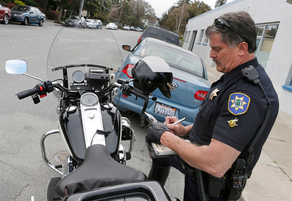 . Redwood City police officer Jim McGee issues a ticket for a driver in Redwood City, Calif., on Wednesday, March 20, 2013.