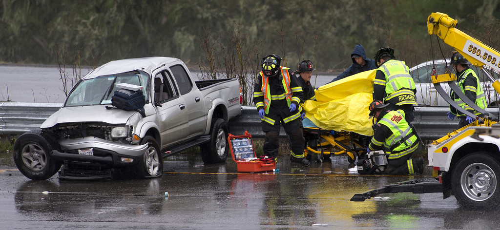 . Firefighters respond to an accident on Interstate 280 in Belmont, Calif., on Tuesday, Feb. 19, 2013. The CHP advises drivers to slow down when the roads are wet. (John Green/Staff)