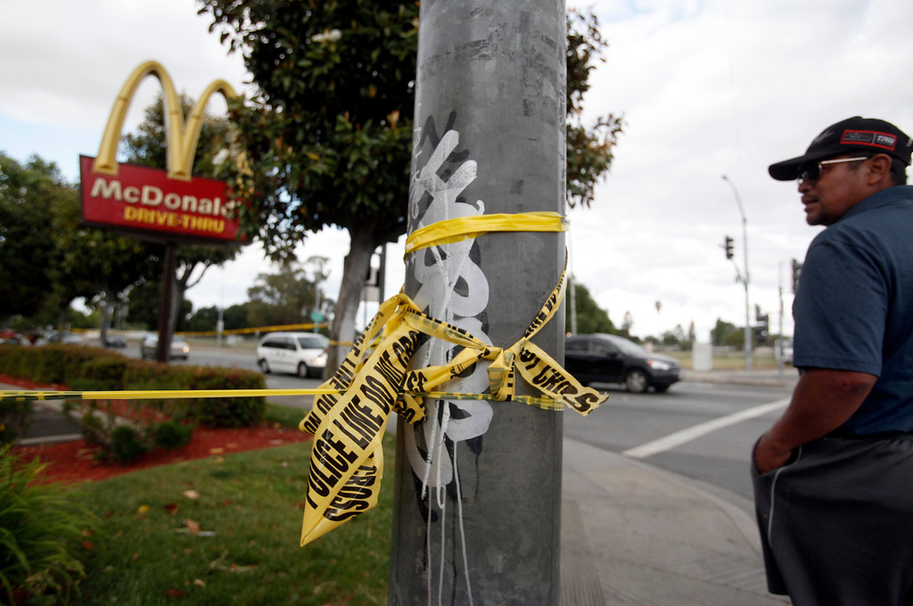. A man peers over police tape at a McDonald\'s where six people, including a 6-year-old child, were shot in broad daylight Sunday afternoon, May 5, 2013, on University Avenue  in East Palo Alto, Calif. (Karl Mondon/Bay Area News Group)