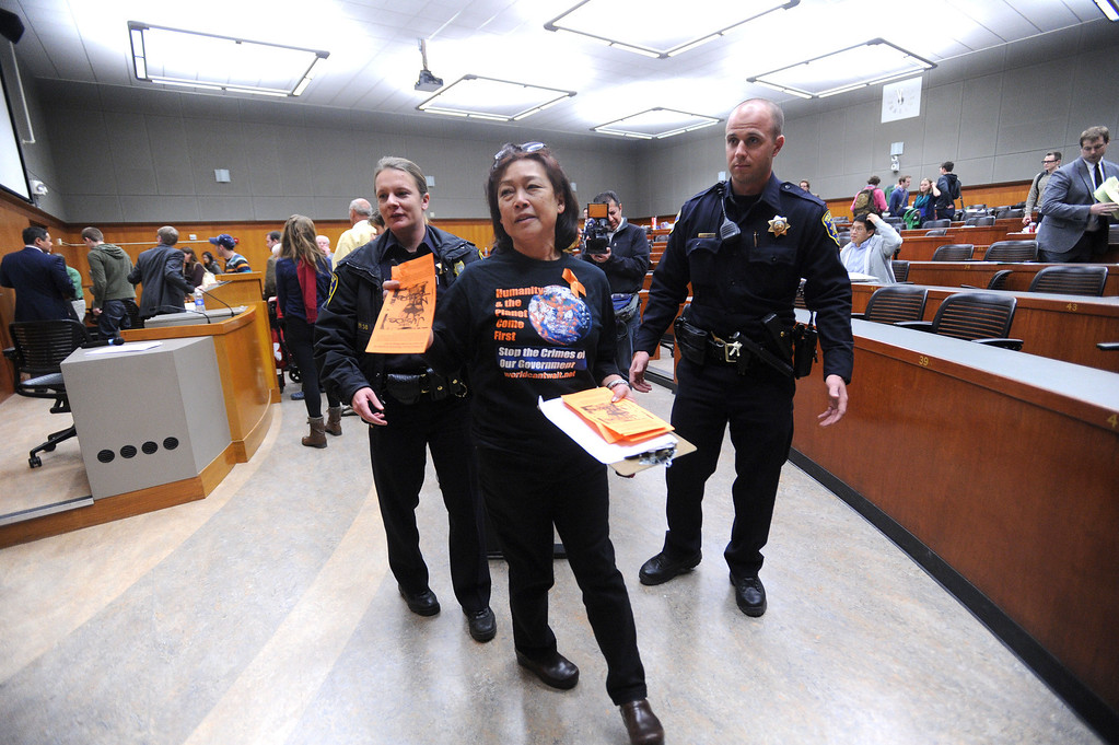 . University police officers escort World Can\'t Wait protester Stephanie Tang from the lecture hall after she entered following an event involving UC Berkeley faculty member John Yoo held in Boalt Hall on the UC Berkeley campus in Berkeley, Calif. on Thursday, Jan. 10, 2013. Some feel that Yoo played a role in the torture program at the United States prison at Guantanamo under the Bush Administration and should not be employed by the university. The event was a debate on Obama Care with University of Saint Thomas School of Law Professor Michael Paulsen sponsored by the Berkeley Federalist Society. (Dan Honda/Staff)