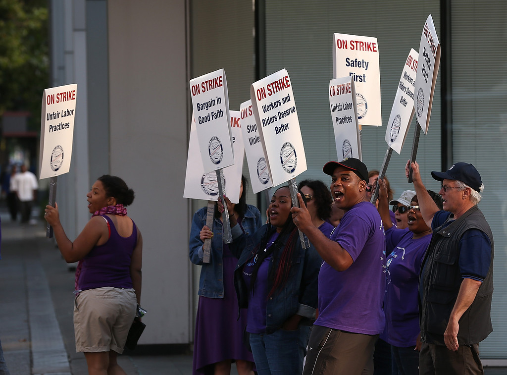 . Amalgamated Transit Union workers hold signs as they strike outside of a Bay Area Rapid Transit (BART) station on July 1, 2013 in Oakland, California. (Photo by Justin Sullivan/Getty Images)