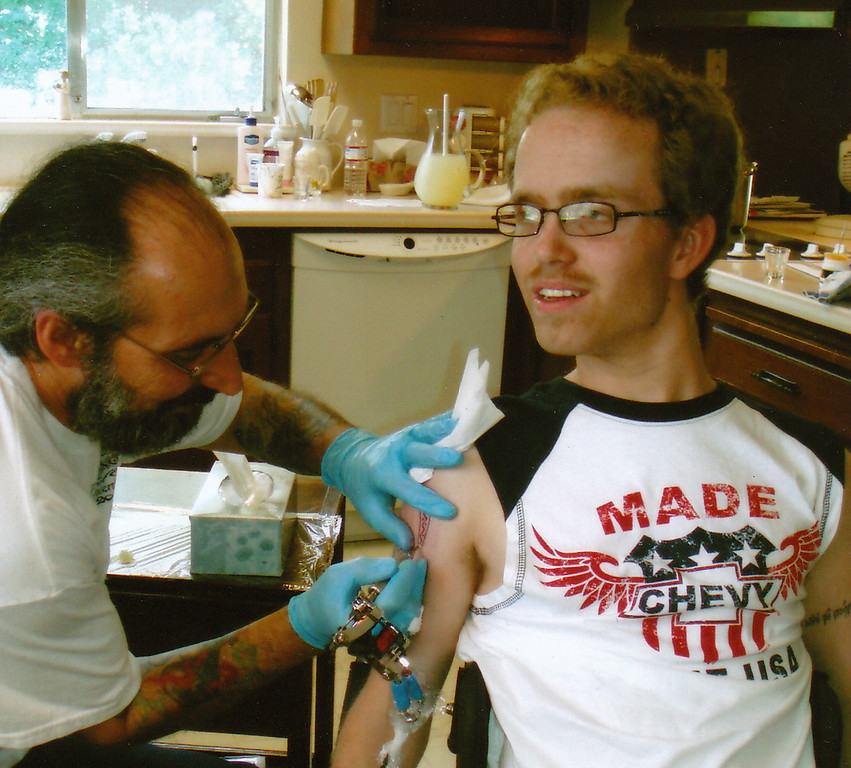 . Phillip Bennett, a Fremont man who died in 2011 of a degenerative muscle disease, gets a tatoo in his Fremont home. (Photo courtesy of Valerie Bennett)
