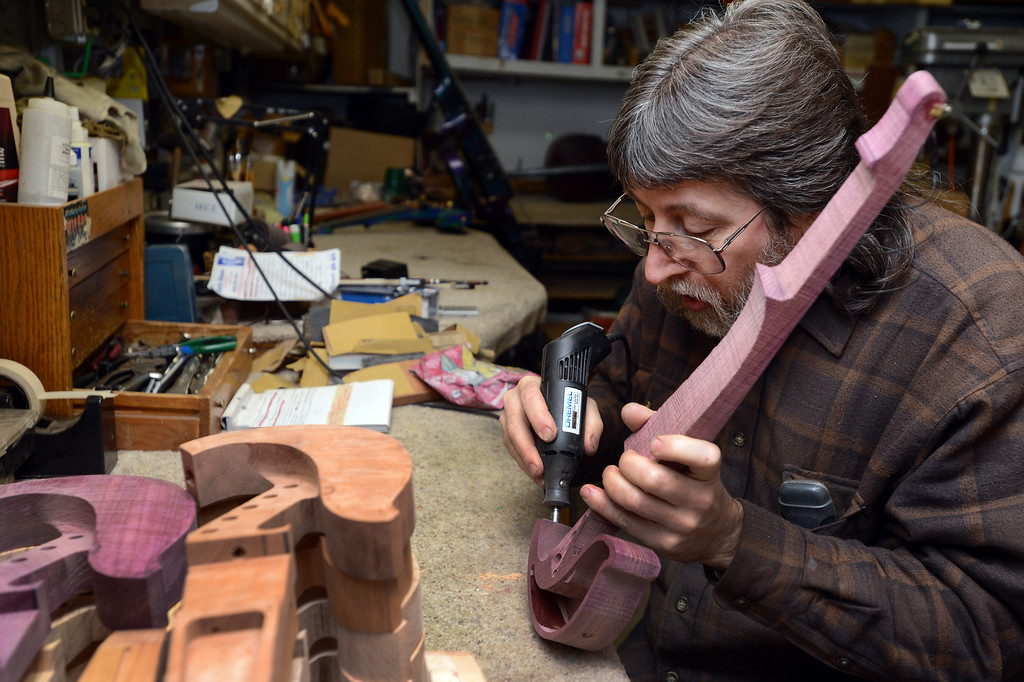 . John Jordan uses a dremel tool to enlarge a hole in an electric violin he is making that will be where the volume switch is placed as he works in his Concord, Calif.  workshop on Monday, Jan. 28, 2013. The wood is found in Bolivia and Brazil and is called purple heart.  (Susan Tripp Pollard/Staff)