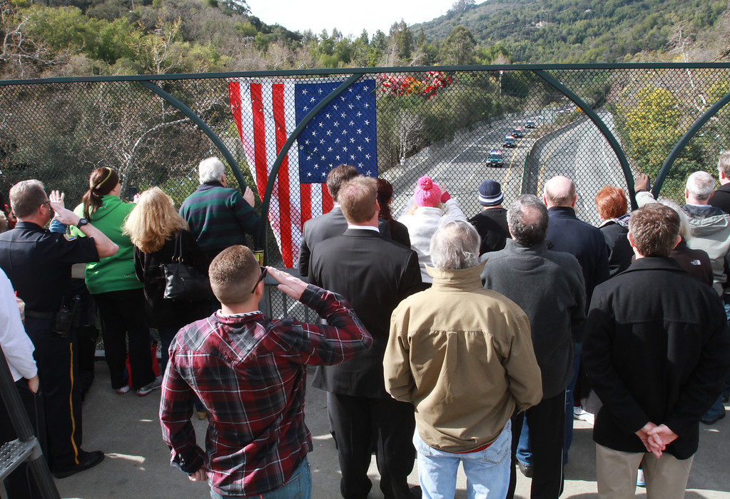 . More than 100 people including local police officers and firefighters gather on the Main Street  overpass in Los Gatos, Calif., to watch and honor the funeral procession for two slain Santa Cruz police officers as it makes its way to San Jose\'s HP Pavilion, and the funeral, on Thursday, March 7, 2013. (George Sakkestad/Bay Area News Group)