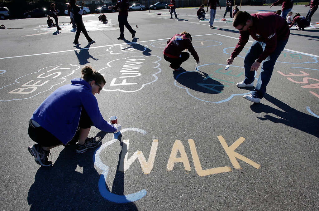 . Kaiser Permanente volunteers repaint the blacktop at Ryan Elementary School during a Dr. Martin Luther King Jr. day-of-service activity in San Jose, Calif. on Monday, January 21, 2013. In the foreground at left is Jaclyn O\'Brien.  (Gary Reyes/ Staff)