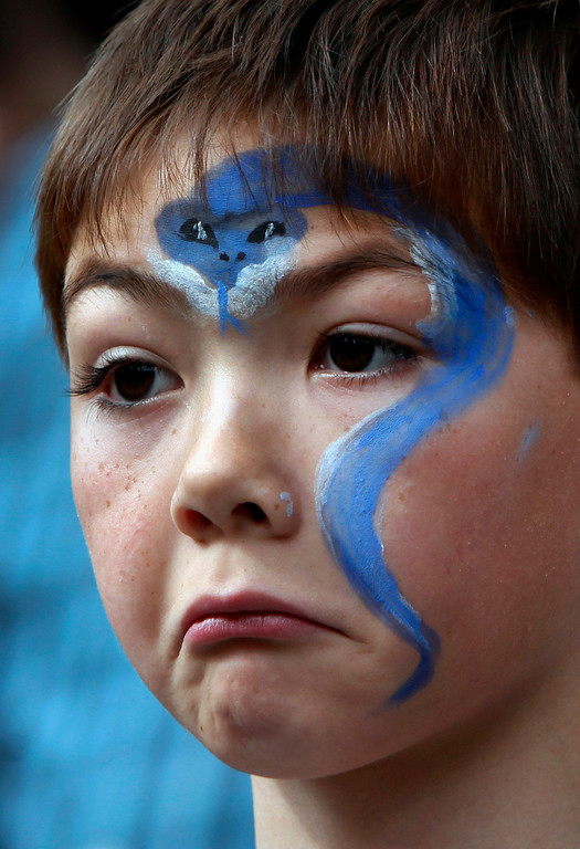 ". Aidan Land, 7, of San Carlos, wearing his Year of the Snake face paint, shows grudging admiration for the dragon dancers from the Asian Cultural Dance troupe performing at the Hakone Estate and Gardens a ""Chinese Village Fair\"" on Sunday afternoon, March 3, 2013 in Saratoga, Calif. (Karl Mondon/Staff)"
