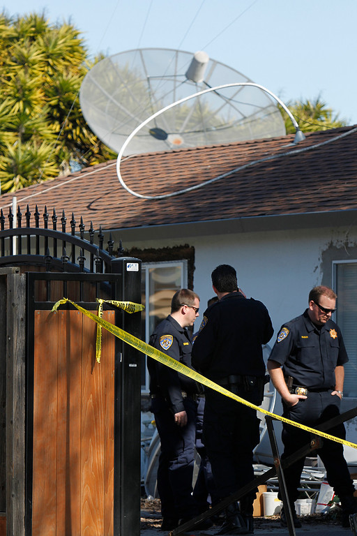 . Members of  the California Highway Patrol confer in back of Everett Basham\'s house on Humbolt Ave., during the search for explosive materials in Santa Clara, Calif. on Wednesday, Feb. 13, 2013.   (LiPo Ching/Staff)
