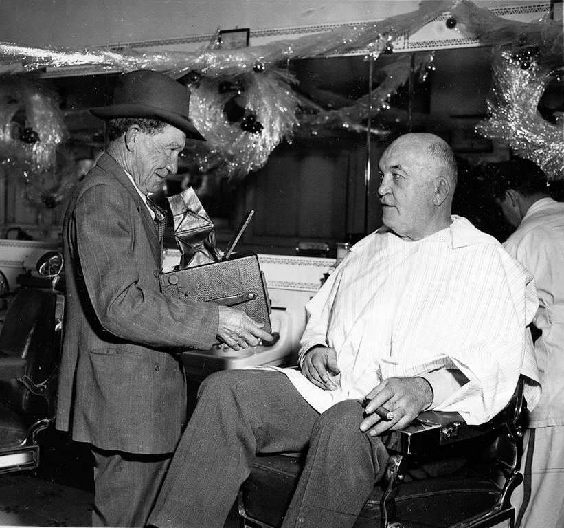 ". Oakland, CA May 10, 1942 - Tribune cameraman \""Doc\"" Rogers and James J. Jeffries reunite at the barber shop located inside the Hotel Lemington. (Oakland Tribune Photo)"
