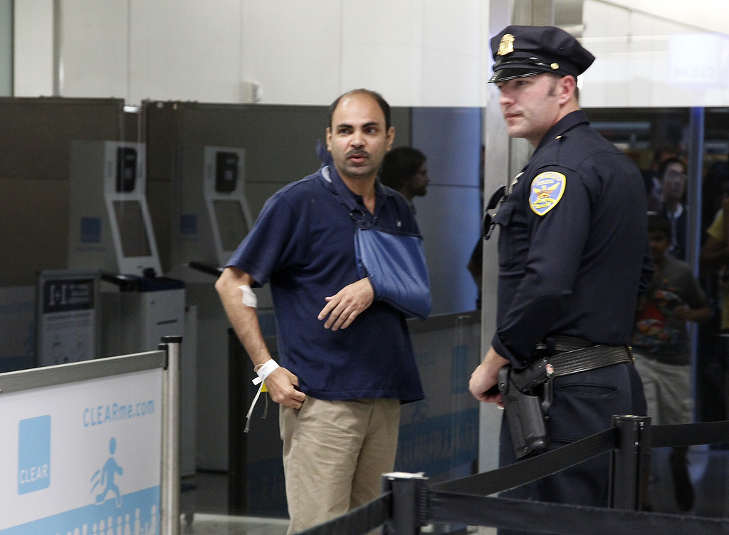 . Vedpal Singh heads to the gate to find his wife after his Asiana Airlines flight 214 from Seoul Korea, crashes at San Francisco International Airport on Saturday July 6,  2013. Singh broke his collarbone and was looking for his wife when he spoke to reporters .  (LiPo Ching / Bay Area News Group)