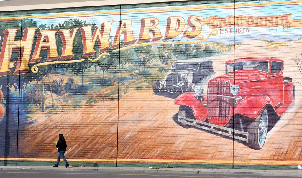 """. A women walks past a large mural bearing the original name for the current city of Hayward, Calif. on Monday, Jan. 30, 2012. The city was known as Haywards until 1894, when the \""""s\"""" was dropped and it officially became the City of Hayward, named after its founder, William Dutton Hayward. Early on it was known as Haywards because of the hotel built by Mr. Hayward, The Haywards Hotel.   (Jim Stevens/Staff Archives)"""