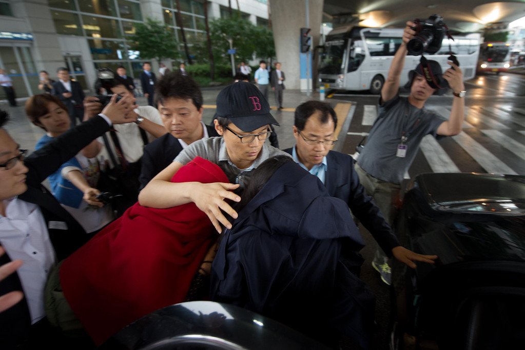 . Two women, their faces covered, reported by local media to be survivors of the Asiana Airlines crash in San Francisco, are escorted into a waiting car after disembarking from a flight at Incheon international airport in Seoul, South Korea, on July 8, 2013. Asiana flight OZ2134 arrived with 11 survivors of an accident in which two people were killed and more than 100 injured when an Asiana Airlines Boeing 777 jet crashed and caught fire as it landed short of the runway at San Francisco International Airport. (Ed Jones/AFP/Getty Images)