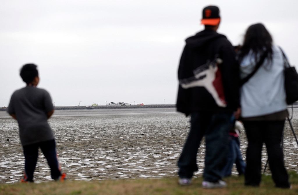 . People watch the wreckage of Asiana Flight 214 after the passenger jet crashed at the San Francisco International Airport in San Francisco, Sunday, July 7, 2013.  Investigators are working to determine what caused the crash of Flight 214 on Saturday. (AP Photo/Marcio Jose Sanchez)