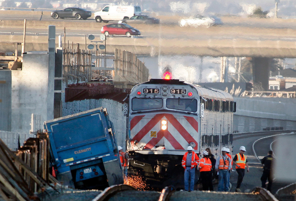 . Crews attempt to cut away a section of truck bed that continued to block a southbound Caltrain after it had struck a big rig earlier in  a non-injury collision at a construction site at the Angus Avenue crossing at 2:30 Monday afternoon Feb. 11, 2013 in downtown San Bruno, Calif.  (Karl Mondon/Staff)