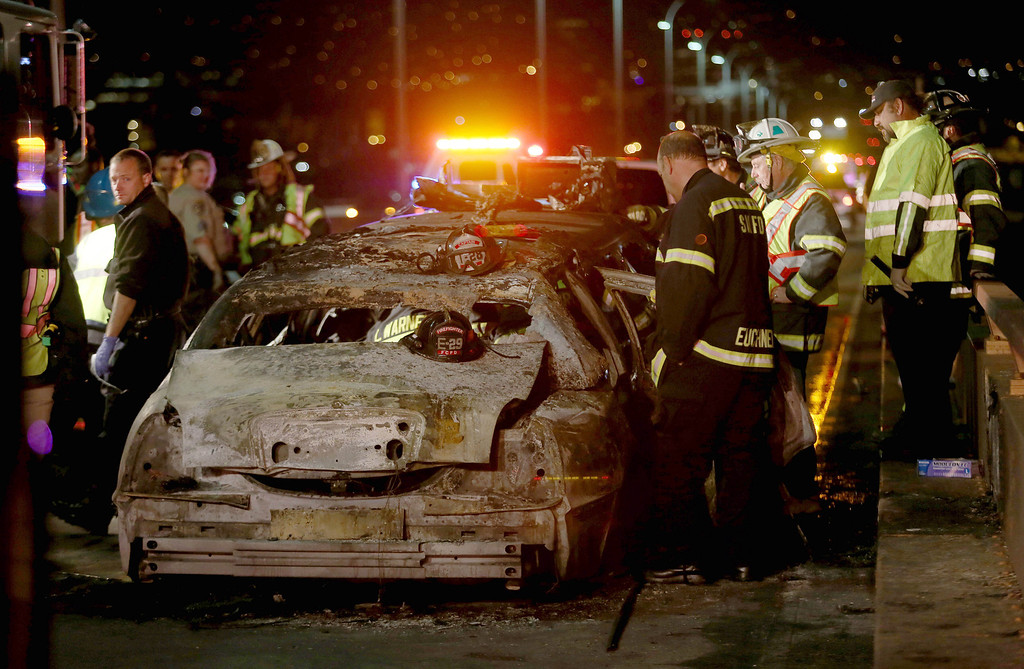 . San Mateo County firefighters and California Highway Patrol investigate the scene of a limousine fire on the westbound side of the San Mateo-Hayward bridge in Foster City, Calif., on Saturday, May 4, 2013. Five women died when they were trapped in the limo that caught fire as they were traveling. Four women and the driver were able to escape.(Jane Tyska/Bay Area News Group)