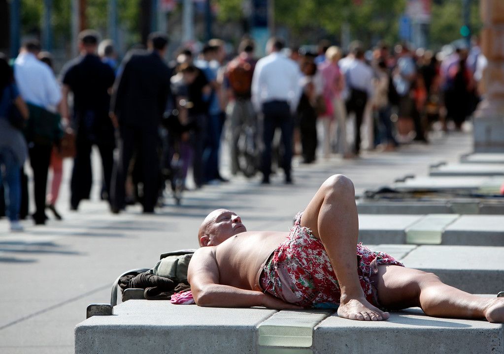 . Not every one is stressed out on the first day of the BART strike. One man worked on his tan as others waited in line for ferries and buses along the Embarcadero in San Francisco, Calif., late Monday afternoon, July 1, 2013. (Karl Mondon/Bay Area News Group)