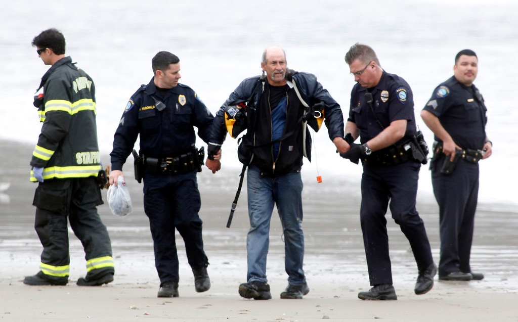 . One of three people rescued from a stolen 82-foot long sailboat named the Darling is arrested by Pacifica police off of Linda Mar Beach in Pacifica, Calif., where the craft grounded early Monday morning March 4, 2013. (Karl Mondon Photo)