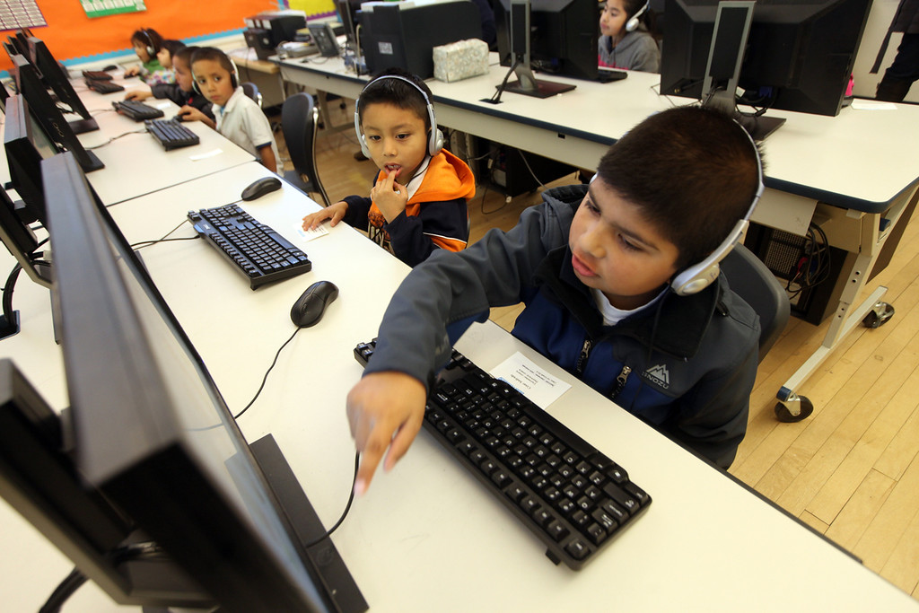 . First grade students Cesar Andrade, 8, right, and Jose Velez, 6, share their learning on the computer in the computer lab at Peres Elementary School in Richmond, Calif., on Friday, Feb. 8, 2013.  Peres school is one of two elementary schools in Richmond that have raised their average API test scores to over 800. (Laura A. Oda/Staff)