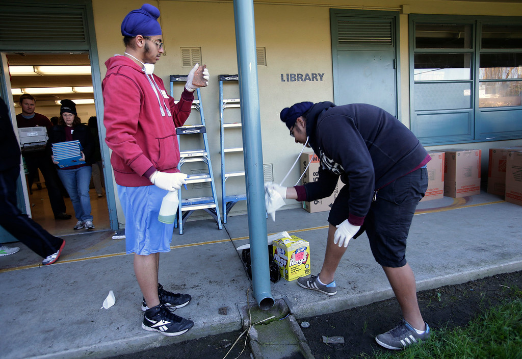. Kabir Loomba, 15, and Sehej Sohal, 15, (l to r) prep a pole for painting as Kaiser Permanente volunteers make improvements at Ryan Elementary School during a Dr. Martin Luther King Jr. day-of-service activity in San Jose, Calif. on Monday, January 21, 2013.   (Gary Reyes/ Staff)