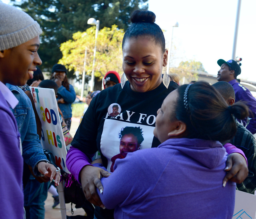 . Nailah Winkfield, center, mother of Jahi McMath, receives hugs and support from family and friends in front of Children\'s Hospital Oakland in Oakland, Calif., on Monday, Dec. 23, 2013. (Susan Tripp Pollard/Bay Area News Group)