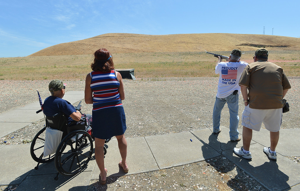 . Earl Batterton, of San Jose, left, a Vietnam war veteran, sits in his wheelchair as his coach Dorothy Bayer, of Antioch, looks on as Wayne Haire, of Brentwood, shoots at a clay target, as his coach Harry Kinney, of Clayton, looks on during the George Findly Memorial Disabled Veteran Trap Shoot at the Bay Point Rod and Gun Club in Concord, Calif., on Saturday, June 15, 2013.  Each vet was assigned a mentor/coach from the club and each got to shoot two sets of flying clay targets.  (Dan Rosenstrauch/Bay Area News Group)