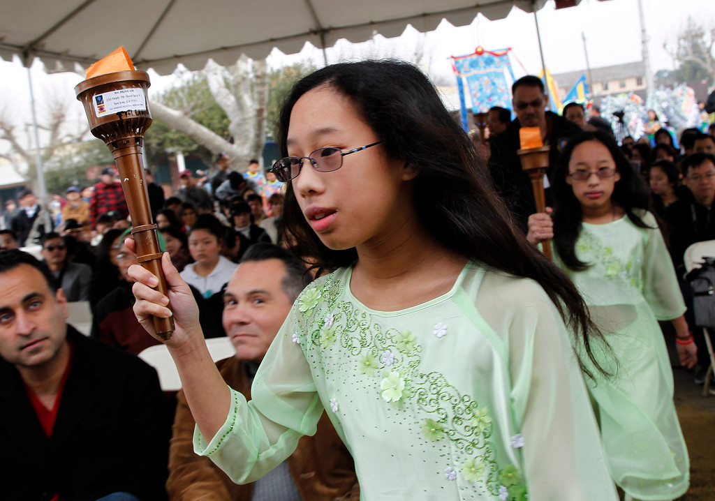 . From foreground left, twins Jacqueline Ta ,12, and Jasmine Ta,12, carry the Freedom Torch at the Tet festival hosted by the Coalition of Nationalist Vietnamese Organizations of Northern California (CONVONCA) at the Santa Clara County Fairgrounds in San Jose, Calif. on Saturday, February 2, 2013.   (LiPo Ching/Staff)