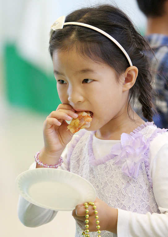 . Alicia Chen, 5, samples a pizza calzone during a �tasting day� at Jane Lathrop Stanford Middle School in Palo Alto on Friday, Aug. 9, 2013. The Palo Alto Unified School District used the free event to showcase 23 new menu items, several of which were touted as local and organic. (Kirstina Sangsahachart/ Daily News)