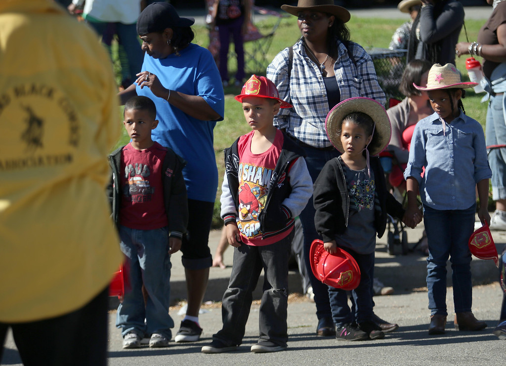 . Children watch cowboys ride during the 39th annual Oakland Black Cowboy Parade and Heritage Festival in Oakland, Calif., on Saturday, Oct. 5, 2013. The event also featured food, entertainment and pony rides for kids at De Fremery Park. The Oakland Black Cowboy Association began in 1975 and educates the public about the role that black cowboys played in history and building of the west. (Jane Tyska//Bay Area News Group)