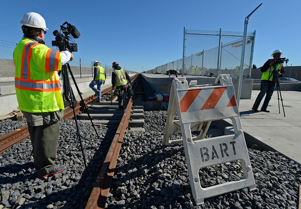 . Members of the media film construction crews working on installing train tracks for the BART platform adjacent to the eBART platform located east of the BART station on Bailey Road  on Highway 4 in Pittsburg, Calif., on Monday, Feb. 11, 2013. Members of the media with state and local city officials traveled on a bus tour of the Highway 4 expansion project in East County. The tour took visitors to construction sites on Railroad Ave and the new eBART station being built on Bailey Road. (Jose Carlos Fajardo/Staff)