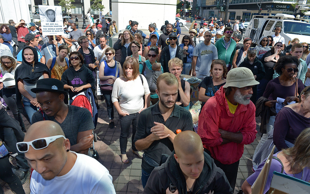 . People gather to listen to speakers while attending a protest at Frank Ogawa Plaza in Oakland, Calif., on Sunday, July 14, 2013. A jury ruled Saturday that defendant George Zimmerman has been found not guilty in the shooting death of Trayvon Martin. (Jose Carlos Fajardo/Bay Area News Group)