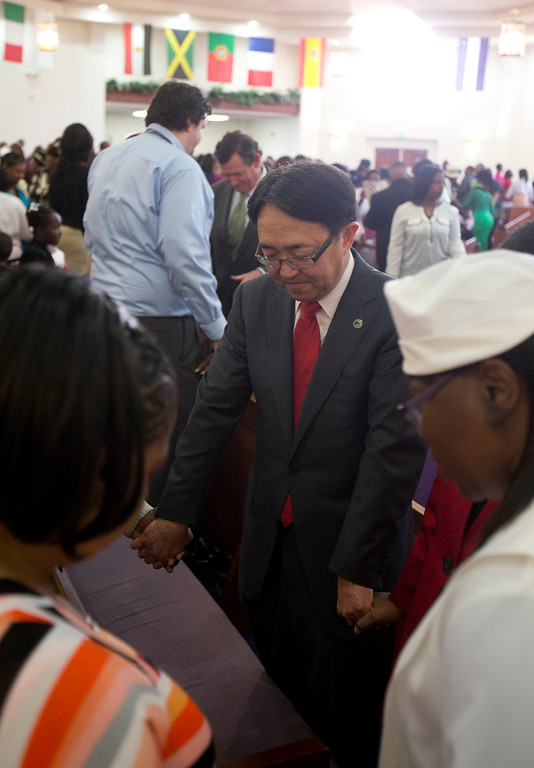 . California State University-East Bay President Leroy Morishita, center, bows his head in prayer with CSU Chancellor Timothy White, in background, during a service at Glad Tidings Church of God in Christ, Sunday, March 10, 2013 in Hayward, Calif. Morishita and White visited the church as part of the annual Super Sunday event to encourage African Americans to attend college. (D. Ross Cameron/Staff)