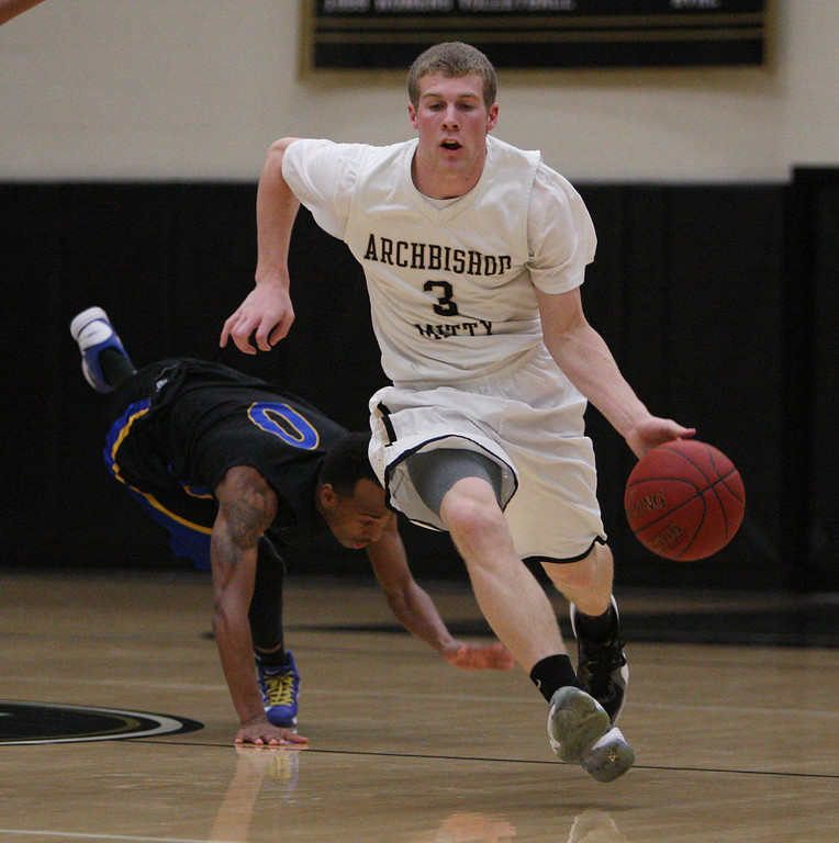 . Mitty\'s Connor Peterson brings the ball down court as Newark\'s Joey Frenchwood falls to the floor in the first half of the NorCal Open Division first round game at Archbishop Mitty High School in San Jose, Calif. on Saturday, March 9, 2013. The Archbishop Mitty Monarchs beat the Newark Memorial High School Cougars, 63-51. (Jim Gensheimer/Staff)