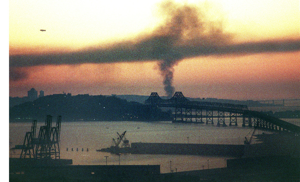 . FILE PHOTO BY BOB PEPPING--Smoke rises behind the Bay Bridge from a fire in San Francisco\'s Marina District caused by the Oct. 17, 1989 earthquake.  The blimp at upper left was in town for the World Series game at Candlestick Park.  One section of the upper deck Bay Bridge collapsed due to the quake.   Picture was shot from helicopter flying over Oakland, Calif.  (Contra Costa Times/Bob Pepping)