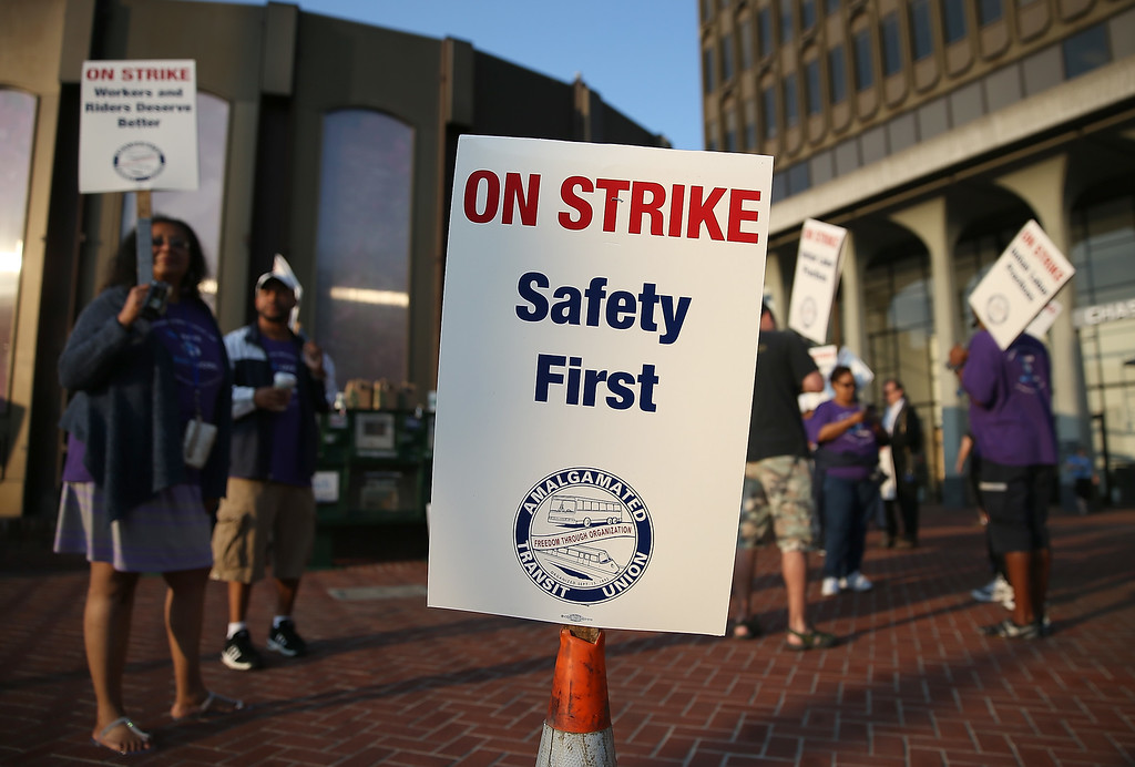 . Amalgamated Transit Union workers hold signs as they strike outside of a Bay Area Rapid Transit (BART) station on July 1, 2013 in Berkeley, California. (Photo by Justin Sullivan/Getty Images)