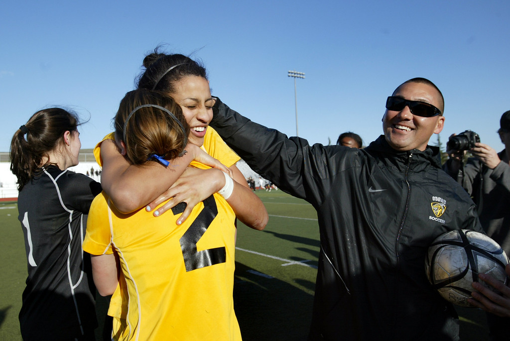 . Bishop O\'Dowd soccer players Lorna McElrath (1),  Ryan Walker-Hartshorn (7), Kate Ranahan (2) and head coach Jon Nishimoto celebrate their North Coast Section Division II Championship against Piedmont at Dublin High School soccer field in Dublin, Calif., on Saturday, Feb. 23, 2013. Bishop O\'Dowd won 3-2 in a series of penalty kicks. (Ray Chavez/Staff)