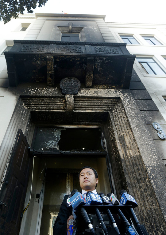 . Wang Chuan, spokesperson for the Chinese Consulate, speaks outside of the damaged entrance to the consulate in San Francisco on Thursday, Jan. 2, 2014. The consulate said Thursday that its compound was damaged in an arson attack and urged American authorities to protect the safety of its diplomats and its premises. (AP Photo/Jeff Chiu)