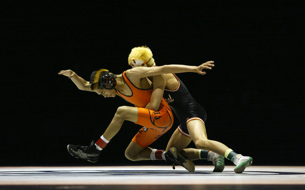 . Vacaville\' Gionn Peralta, left, struggles against Central\'s Adrian Composano in the 106-pound championship match during the California Interscholastic Federation wrestling championships in Bakersfield, Calif., on Saturday, March 2, 2013. Composano would go onto win the match 11-10. (Anda Chu/Staff)