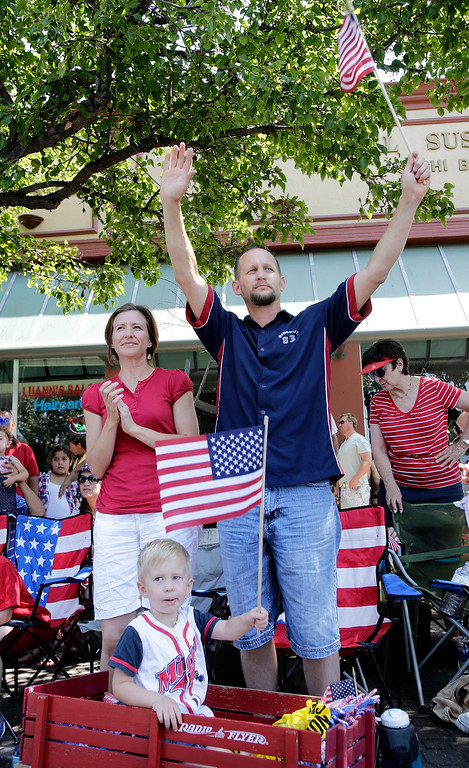 . Ted and Michelle Korosy and their son Eli, 2, cheer on the participants in the annual Fourth of July parade in Redwood City, Calif. on Thursday, July 4, 2013. Considered the largest Independence Day parade in Northern California, it is celebrating its 75th year. (Gary Reyes/Bay Area News Group)
