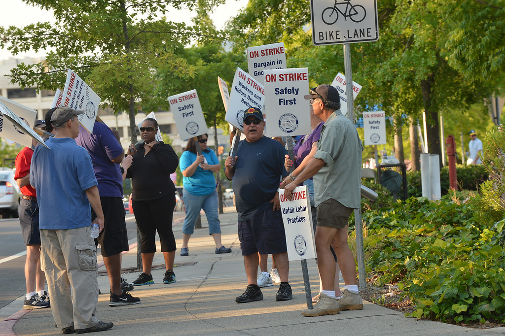 . A group of BART strikers stand in front of the Walnut Creek BART station just up the street from a long line of commuters entering buses to take them to the San Francisco on the second day of the BART strike in Walnut Creek, Calif., on Tuesday, July 2, 2013.  (Dan Rosenstrauch/Bay Area News Group)