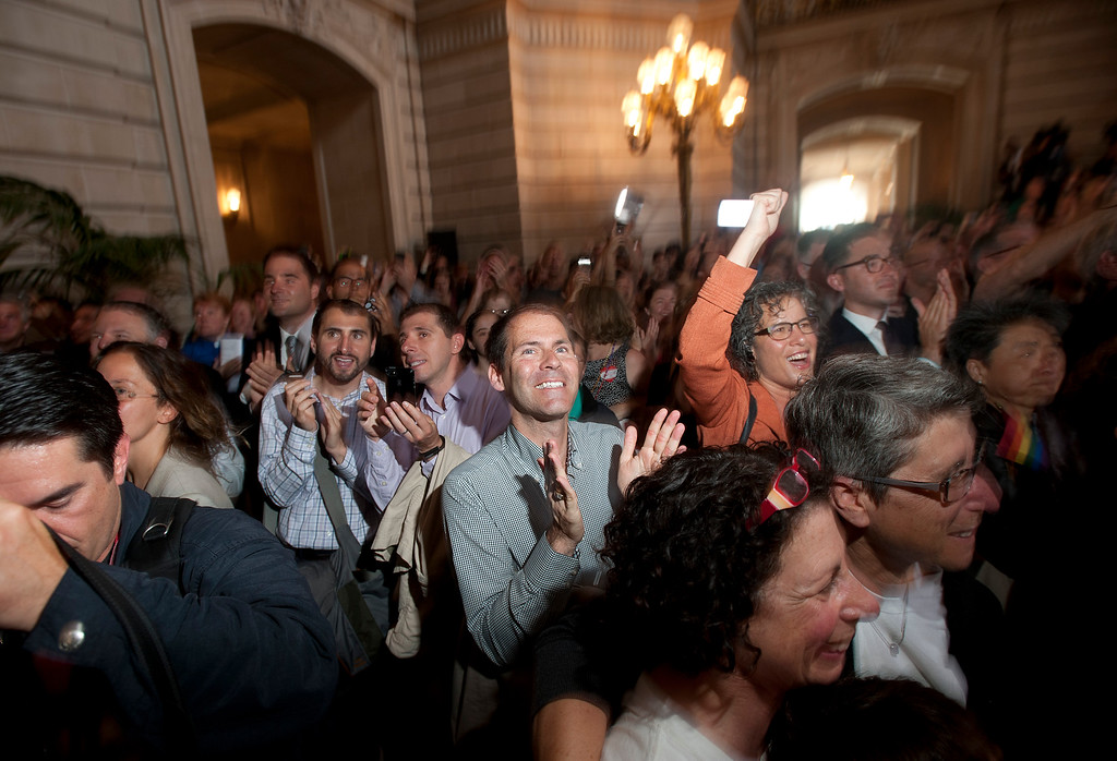 . Gay rights activists celebrate shortly after a U.S. Supreme Court decision that cleared the way for same-sex marriage in California, at San Francisco\'s City Hall on Wednesday, June 26, 2013.  The justices issued two 5-4 rulings in their final session of the term. One decision wiped away part of a federal anti-gay marriage law that has kept legally married same-sex couples from receiving tax, health and pension benefits. The other was a technical legal ruling that said nothing at all about same-sex marriage, but left in place a trial court\'s declaration that California\'s Proposition 8 is unconstitutional.(AP Photo/Noah Berger)
